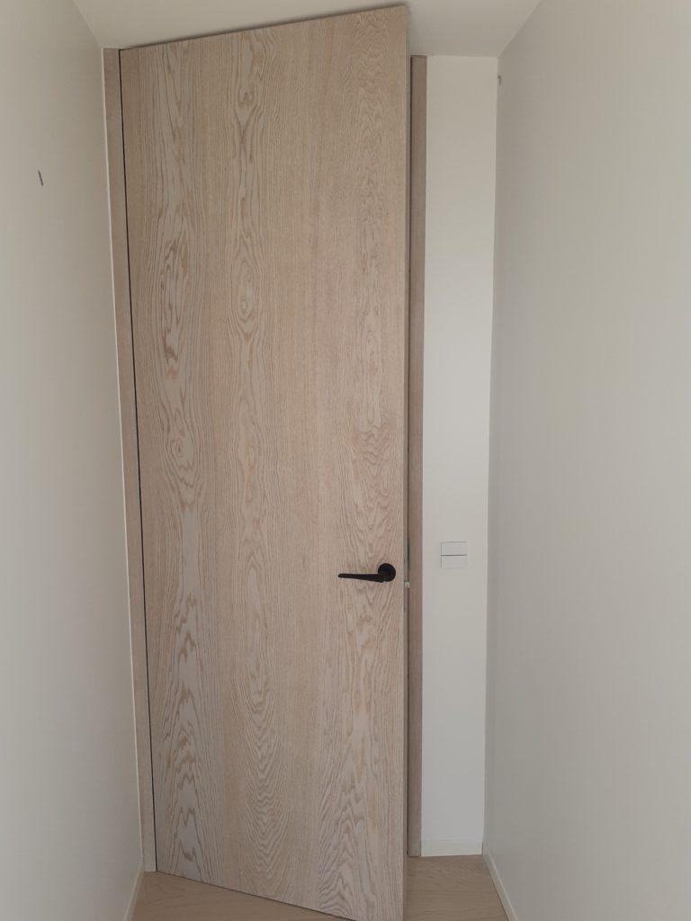 Høje, uindfattede døre i børstet egefinér til modernistisk villa