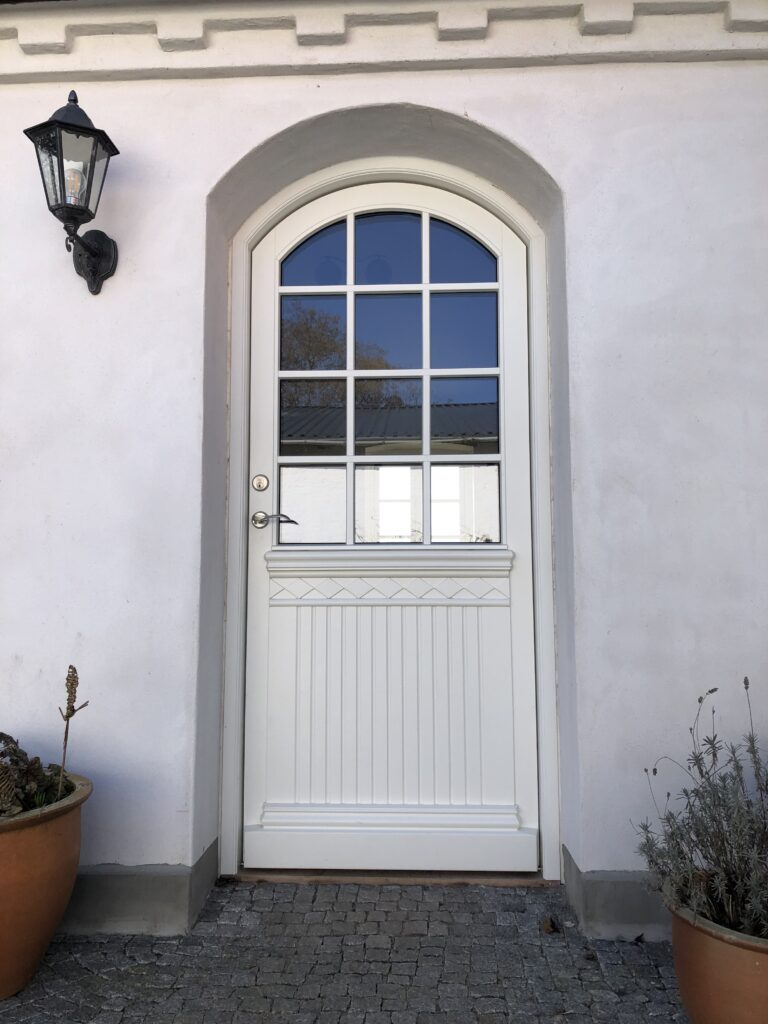 Personlig hoveddør med bue og udsmykninger i dørbladet under de småsprossede vinduer. Specialfremstillet af Madsen Vinduer og Døre.