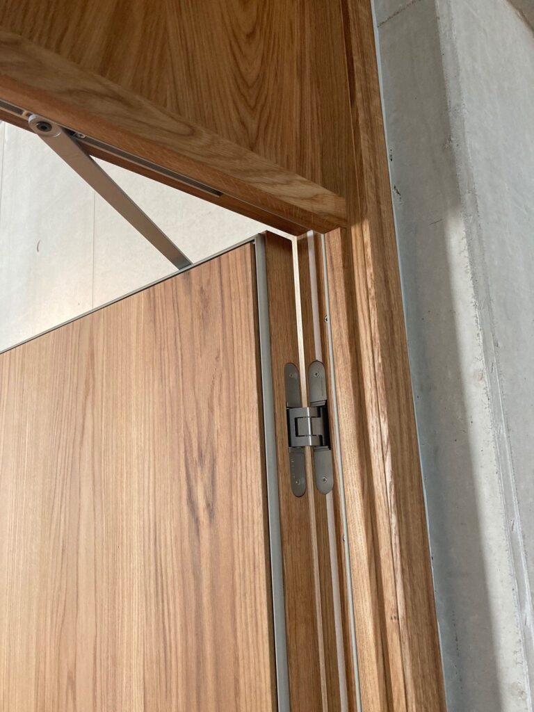 Skjult dørpumpe og hængsler på indvendige døre. Dørene er lavet med et 40 cm højt overstykke i egeplanker som dørbladet. Derved fremstår dørene højere i det højloftede formidlingsrum.